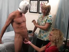Blonde nurses give a precautionary prostate exam to a patient