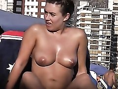 Tanning oil makes her naked tits look fantastic