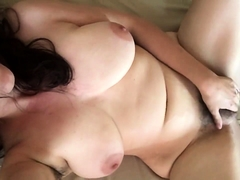 Busty brunette wife lies on her back and rubs her hairy cunt